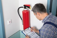 Professional Checking A Fire Extinguisher. Close-up Of A Male Professional Checking A Fire Extinguisher Using Clipboard Royalty Free Stock Photos