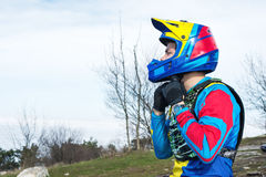 Close-up Male racer mtb cyclist in protective outfit preparing for race buttoning full face helmet. Close-up Male racer mtb cyclist in protective outfit prepares Stock Photo
