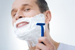 Close up of a male razor. Smooth shaving. Close up of a male razor being in hands of a positive delighted man while shaving Stock Image