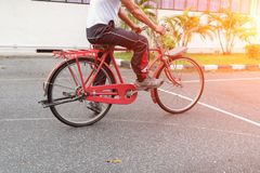 Close up male ride a bicycle red classic vintage in former beautiful with sunset light tone.  Royalty Free Stock Photography