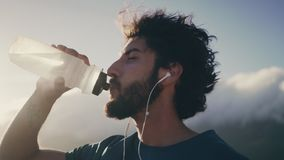 Thirsty male runner drinking the water from bottle stock footage