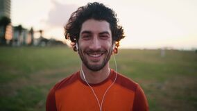 Close up of male runner in earphones looking seriously at camera during morning workout