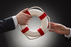 Close-up of a male's hand holding lifebuoy. Close-up Of Two Businessman's Hand Passing Lifebuoy Stock Images