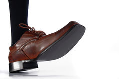 Close-up of male shoe stepping on white background Royalty Free Stock Images
