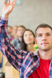 Close up of a male student raising hand by others in classroom. Close up of a young male student raising hand by others in a row at the classroom Royalty Free Stock Image