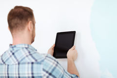 Close up of male with tablet pc with blank screen. Repair, building, technology and home concept - close up of male with tablet pc with blank screen next to Royalty Free Stock Images