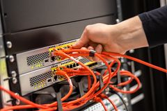 Close-up of Male Technician Plugging Network Cable In Network Router. Cropped hand of male technician plugging network cable in router cluster at datacenter royalty free stock photos