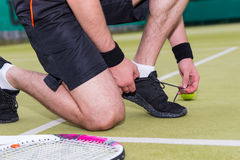 Close up male tennis player tying shoelaces Royalty Free Stock Images