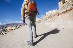 Close-up of male traveler walking uphill on sand dune leading to monastery in Leh, Ladakh, India.  Stock Photo