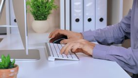 Close up male typing on white keyboard. Manager working on computer. unrecognizable busineess man sitting at the desk with flower pot folders and pc display stock footage