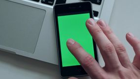 Man using smartphone. Close up - Male using smartphone with green screen in home, Man scrolling modern device lying on the laptop on white table stock video