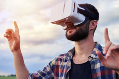 Close-up of male using VR glasses outdoors. Low angle of bearded Caucasian man wearing VR glasses. Zooming object. Virtual reality, modern technology Royalty Free Stock Image