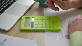 Close-up Man accountant hand holding pen counting on calculator. Businessman Doing Calculations