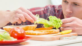 Close up of man adding lettuce leaves to sandwich stock video footage