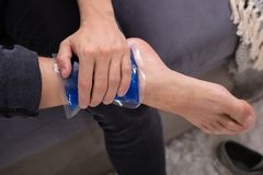 Man Applying Ice Gel Pack On An Ankle. Close-up Of A Man Applying Ice Gel Pack On An Injured Ankle stock image