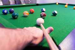 Close up of Man arm playing Snooker Pool green table in a modern games room. Man& x27;s arm playing pool about to shoot the white ball to the whole snooker balls Stock Photo
