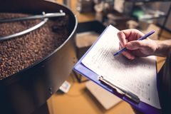 Male hands writing information about roasting beans stock photos