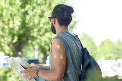 Close up of man with backpack and map in city. Travel, tourism, backpacking and people concept - close up of man traveling with backpack and map in city Royalty Free Stock Image