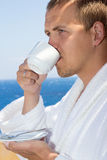 Close up of man in bathrobe drinking coffee on balcony Stock Photos