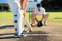 Close up of man batting while playying cricket at field. On sunny day stock image