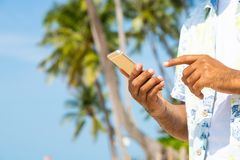 Man on the beach using smartphone. stock image