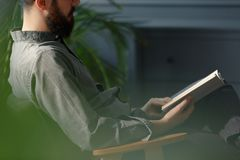 Close-up of man with beard in grey shirt reading book stock photo