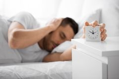 Close up of man in bed reaching for alarm clock. Morning and people concept - close up of sleepy young man in bed reaching for alarm clock on bedside table at stock photos