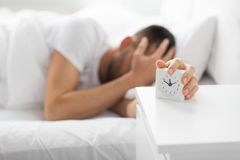 Close up of man in bed reaching for alarm clock. Morning and people concept - close up of sleepy young man in bed reaching for alarm clock on bedside table at royalty free stock images