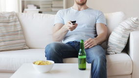 Close up of man with beer and remote at home stock footage