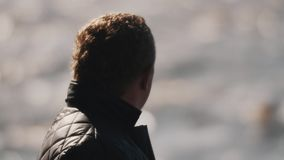 Close up of a man in black vest looking at lake waters. Blurry background stock video