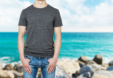 Close-up of a man in a blank grey t-shirt. Hands in the denims pockets. Stock Photo