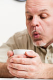 Close up of man blowing into cup Stock Photo