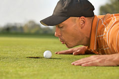 Close-up of man blowing on golf ball Royalty Free Stock Images