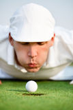 Close-up of man blowing on golf ball. Desperate golfer blowing on golf ball to put in hole, funny golfing cheat - concept Stock Photos