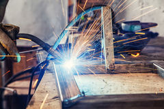 Close up man brews a metal. A close-up of welding a metal with a welding machine on a wooden table at the factory, multi-yellow and blue sparks fly apart Royalty Free Stock Images
