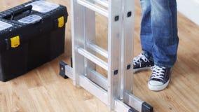 Close up of man bringing tool box and ladder