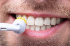 Close-up Of A Man Brushing Teeth. With Electric Brush royalty free stock image