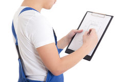 Close up of man builder in blue uniform writing something on blu Stock Photo