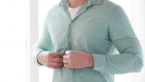Close up of man buttoning his shirt at home Stock Images
