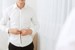 Close up of man buttoning white shirt Stock Images