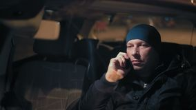 Close-up, Man Talking on the Phone Sitting at the Wheel of a Car at Night in the Parking stock footage
