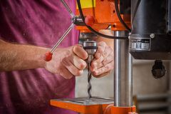 Close up drilling   machine. Close-up of a man carpenter in work clothes drilling  on an orange large measuring machine in a light workshop Royalty Free Stock Image