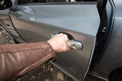 Close-up of man in casual wear opening a front car door royalty free stock photos