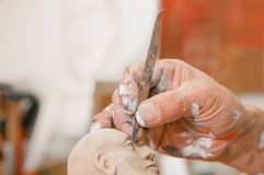 Close up of man ceramist hands holding a tool and working on sculpture details of the head on wooden table in workshop Stock Photography