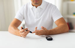 Close up of man checking blood sugar by glucometer. Medicine, diabetes, glycemia, health care and people concept - close up of man checking blood sugar level by Stock Photo