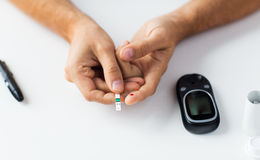 Close up of man checking blood sugar by glucometer Stock Photos