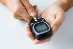 Close up of man checking blood sugar by glucometer Royalty Free Stock Photos