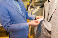 Close up of man choosing clothes in clothing store. Sale, shopping, fashion, style and people concept - close up of elegant young man in jacket choosing clothes Royalty Free Stock Photo