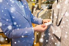 Close up of man choosing clothes in clothing store Royalty Free Stock Photos