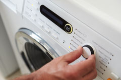 Close Up Of Man Choosing Cycle Program On Washing Machine Royalty Free Stock Photos